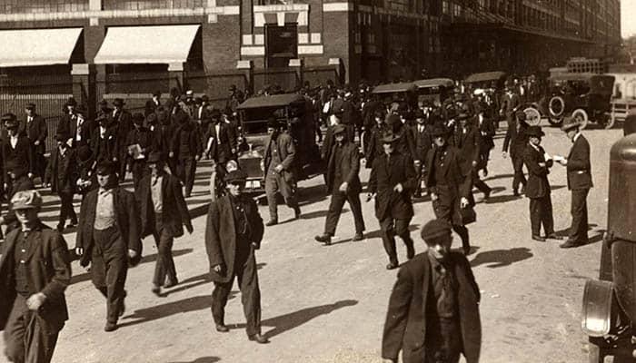 Trabajadores saliendo de la fábrica de Ford Motor Company, ejemplo de división del trabajo