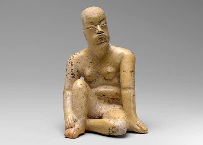 Estatua de un hombre olmeca sentado.