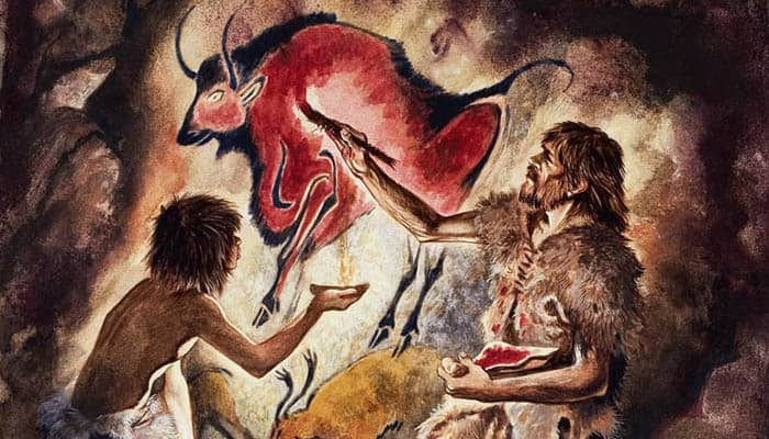 Un hombre pinta un bisonte en una cueva